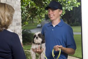 Smiling dog walker dropping off a dog to its female owner